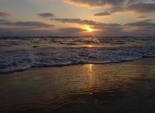 Solnedgångsikt på en lugna sandig strand med molnig himmel och guld- ljus royaltyfri foto