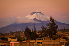 Solnedgångsikten av den Cotopaxi vulkan från den Latacunga staden, Ecuador Royaltyfri Foto