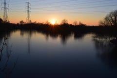 Solnedgångskog och sjö Arkivfoto