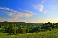Solnedgångsky ovanför kullarna Arkivbild