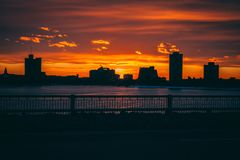 Solnedgångsoluppgång bak stadsbyggnader arkivbild
