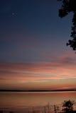 Solnedgångstående i den guld- sjön och himlen och månen för pik den blåa Royaltyfri Foto