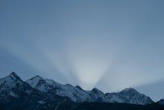 Solnedgångstrålar över bergskedjan arkivfoto