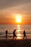 Solnedgångstrand med ungar som spelar fotboll Arkivbild