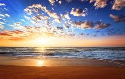 Solnedgångstrand med vågor och molnigt royaltyfria foton