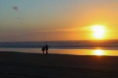 Solnedgångstranden går Arkivbild