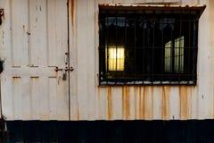 Solnedgångthroung ett svart fönster royaltyfria bilder