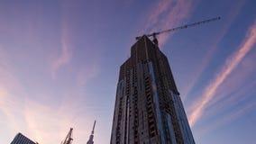 Solnedgångtimelapse av skyscrapperbyggnationer, zoomar ut lager videofilmer