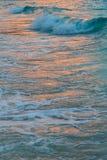 Solnedgångvågor och hav Arkivfoto