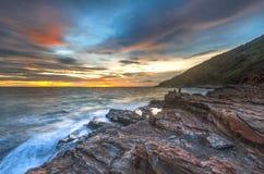 Solnedgångvågor piskar linjen inverkan vaggar på stranden Arkivfoton