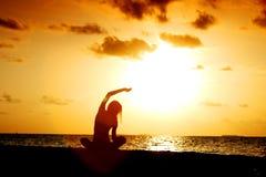 Solnedgångyogakvinna arkivfoto
