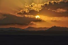 Solnedg?ng ?ver bergen med solen som skiner till och med molnen royaltyfri foto