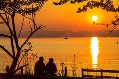 Solnedgång bredvid sjön Arkivbild