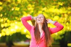 Solnedgång i parkera Ståenden som skrattar flickakvinnan i höstligt, parkerar skogen Arkivfoton