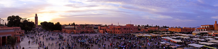 Solnedgång på den Djemaa el Fna marknaden i Marrakesh, Marocko, med Koutu Royaltyfri Foto