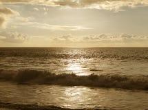 Solnedgång på stranden i sepiasignal Arkivfoto