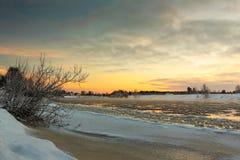 Solnedgång över den frysa floden Arkivfoto