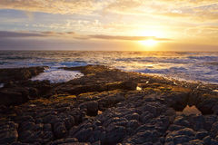 Solnedgång över den steniga kustlinjen Arkivfoto
