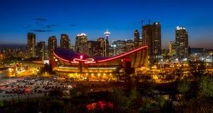 Solnedgång över i stadens centrum Calgary och Saddledome Royaltyfri Foto