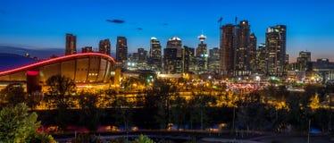Solnedgång över i stadens centrum Calgary och Saddledome Royaltyfri Fotografi