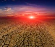 Solnedgång över sprucken jord Arkivfoton