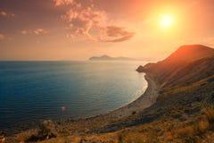 Solnedgång över stenig havskust Royaltyfri Foto