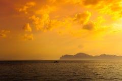 Solnedgång över stenig havskust Royaltyfria Bilder