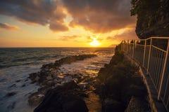 Solnedgång över stenig havskust Arkivfoton