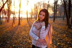Solnedgångståenden av den unga kvinnan för den härliga brunetten i höst parkerar Arkivfoto