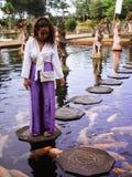 Solo Żeński podróżnik Karmi Koi ryby na odskoczniach do czegoś wokoło Koi ryby przy Główną fontanną przy Tirta Gangga, Bali obrazy royalty free