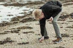 Solo adolescente cogiendo la piedra en la playa Fotos de archivo