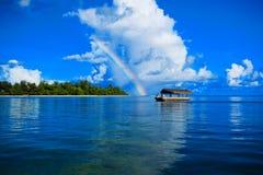 Solo barco en el ver bajo el arco iris Foto de archivo