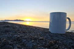 A solo blank coffee mug on the bug filled shoreline stock images