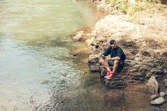 Solo caminante masculino que usa la tableta en la naturaleza mientras que se sienta en orilla rocosa del río fotos de archivo libres de regalías