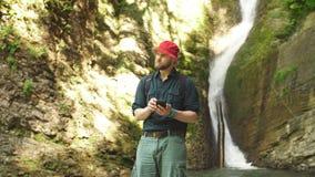 Solo caminante masculino que usa la tableta en la naturaleza mientras que se sienta en orilla rocosa del río almacen de video