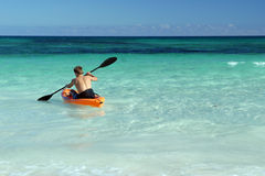 Solo canoeist paddling in sea. A solo canoeist paddles out to sea with his back facing the camera Royalty Free Stock Image