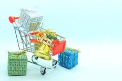 Solo carro de la compra con cuatro cajas de regalo y la campana de oro Foto de archivo libre de regalías