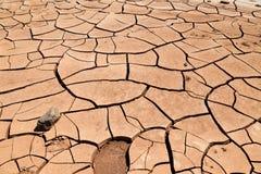 Solo de argila rachado na frente das montanhas flamejantes província em China, Xinjiang Localizado na depressão de Turpan fotografia de stock