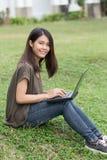 Solo estudiante adolescente asiático de la sonrisa que usa el ordenador portátil Imagen de archivo