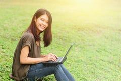 Solo estudiante adolescente asiático de la sonrisa que usa el ordenador portátil Fotos de archivo libres de regalías