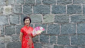 Solo female tourist in chinese traditional clothing with stone wall. Solo female tourist in chinese traditional clothing Qipao with stone wall stock image