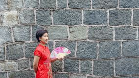 Solo female tourist in chinese traditional clothing with stone wall. Solo female tourist in chinese traditional clothingQipao with stone wall royalty free stock image