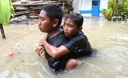 Solo flood. People saving achild when flood came in Solo, central java, indonesia stock image