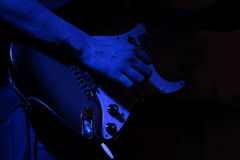 Solo guitar in a blue light. Playing guitar in a blue light royalty free stock photography