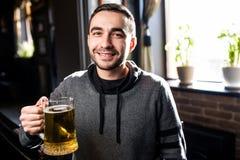 Solo hombre en un pub o una barra que sostiene la taza la cerveza alta en el aire para las alegrías Fotos de archivo libres de regalías