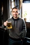 Solo hombre en un pub o una barra que sostiene la taza la cerveza alta en el aire para las alegrías Fotografía de archivo libre de regalías