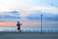 Solo hombre que corre en una 'promenade' al lado de la playa en la salida del sol Nubes y luz del sol imagenes de archivo
