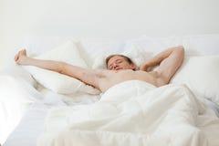 Solo hombre que despierta en cama Imagenes de archivo