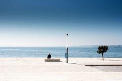 Solo hombre que se sienta en un banco y que mira el mar. Triste solo Imagenes de archivo