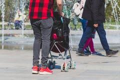 Solo inconformista solo del padre en camisa roja y negra a cuadros con un cochecito que camina en el parque de la ciudad fotografía de archivo libre de regalías